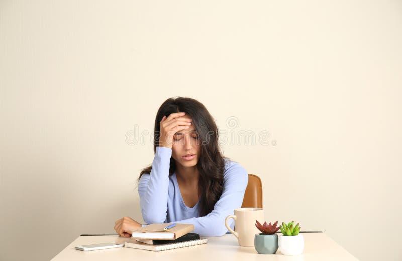 坐在桌上的被注重的年轻女人在办公室 免版税库存照片