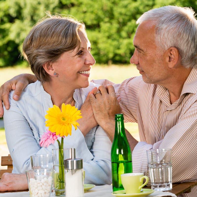 坐在桌上的退休的夫妇握手 免版税库存图片