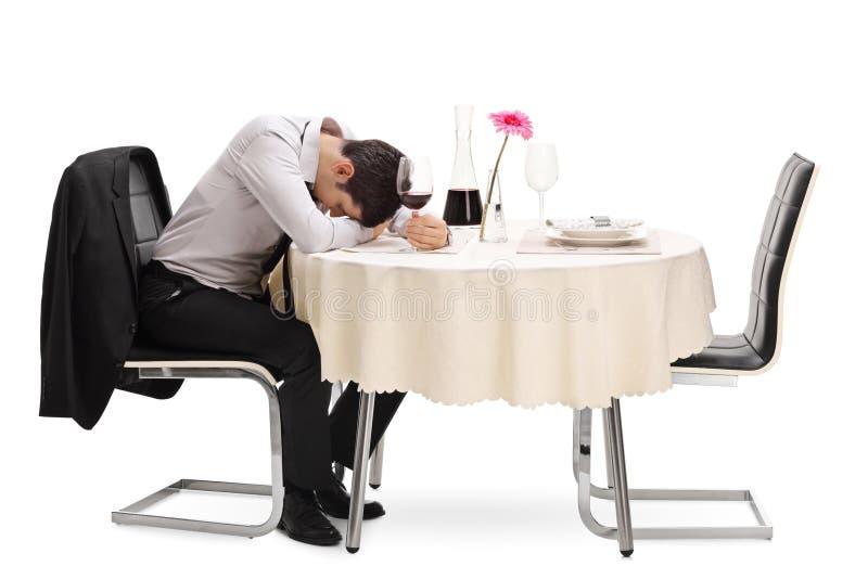 坐在桌上的醉酒和孤独的人 免版税库存图片