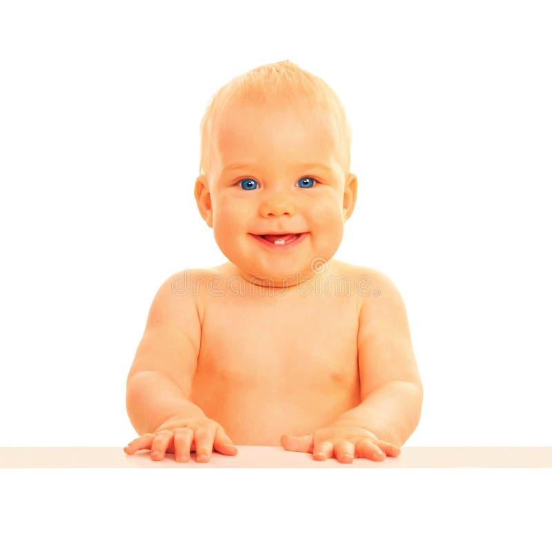 坐在桌上的婴孩,微笑和愉快 图库摄影