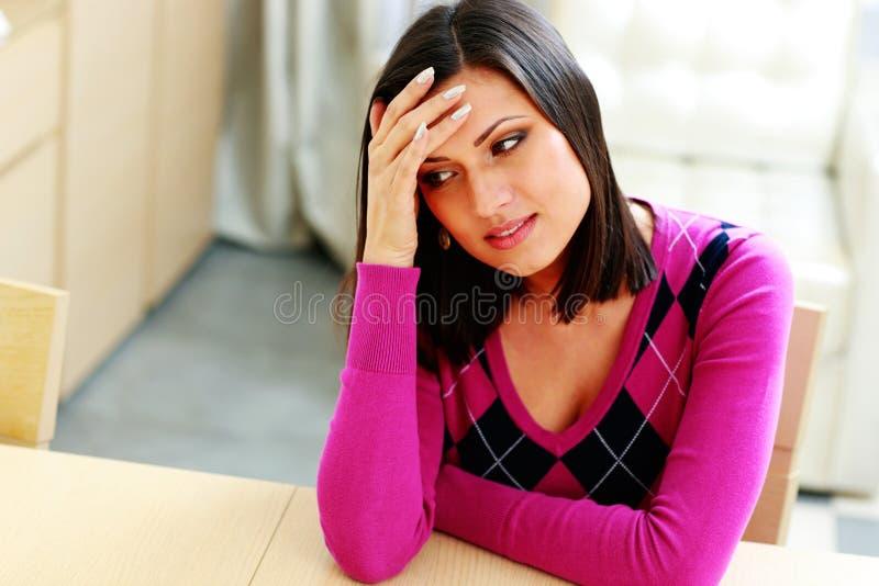 坐在桌上的年轻沉思妇女 库存照片