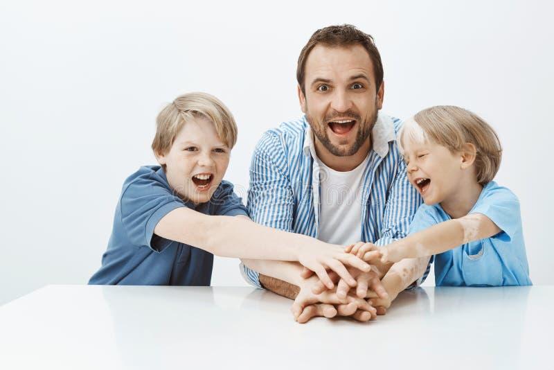 坐在桌上,握手,笑和呼喊从幸福的快乐的可爱的男孩和父亲室内射击  库存照片