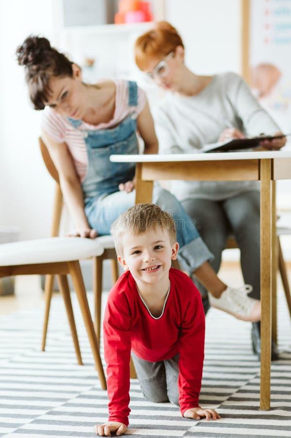 坐在桌下的粗鲁的孩子在ADHD的疗法期间与他的母亲和专业治疗师 图库摄影