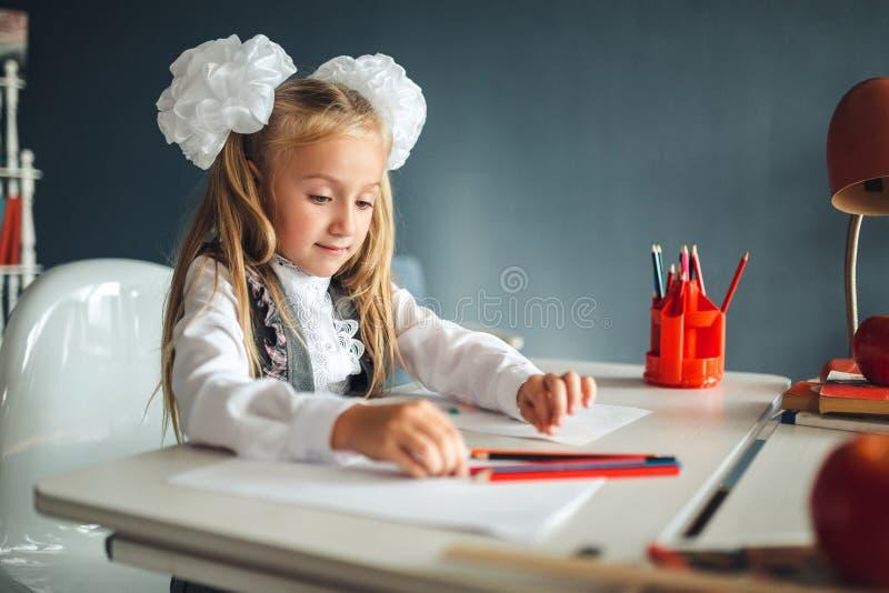 坐在桌和画上的逗人喜爱的女小学生 一美女的画象在教室 一点有白色弓的女小学生 免版税图库摄影