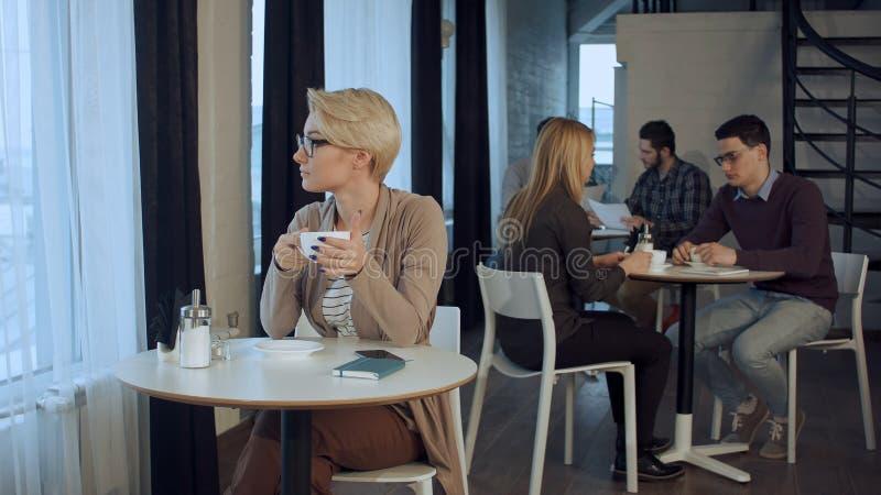 坐在桌和饮用的咖啡上的年轻美丽的妇女室内 免版税库存照片