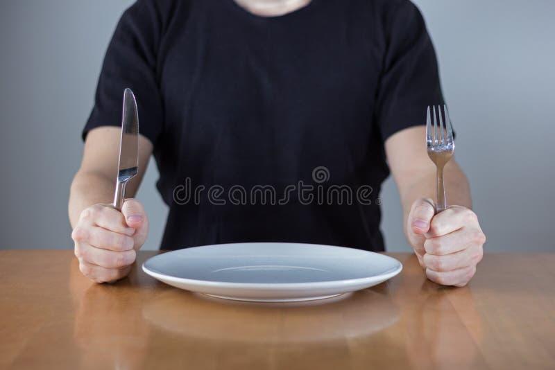 坐在桌等待的食物的人 免版税图库摄影