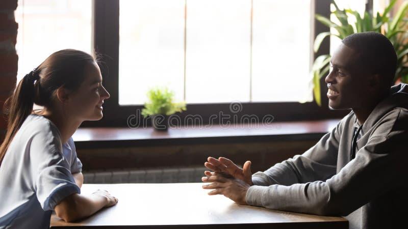 坐在桌聊天的不同的千福年的正面夫妇感到好 免版税库存照片
