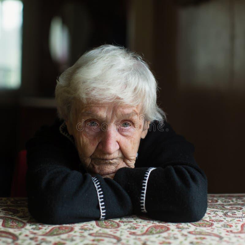 坐在桌边的老妇人画像 库存照片
