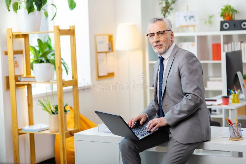 坐在桌边缘的灰色成套装备的殷勤悦目整洁的人 免版税图库摄影