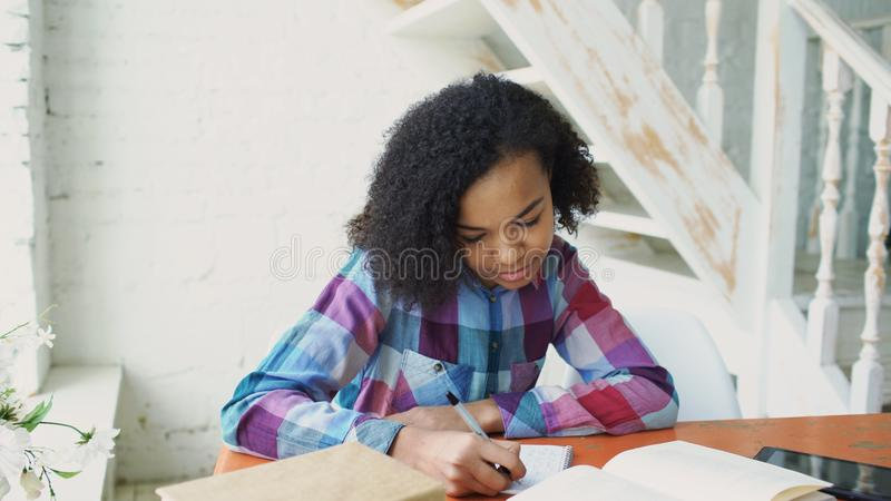 坐在桌集中的少年卷发的混合的族种女孩被聚焦吸取考试的教训 免版税图库摄影