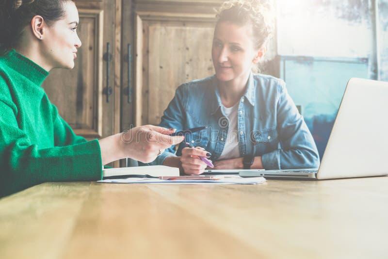 坐在桌,候宰栏上的两个年轻女商人和谈论战略 在桌上是膝上型计算机,文件 免版税图库摄影