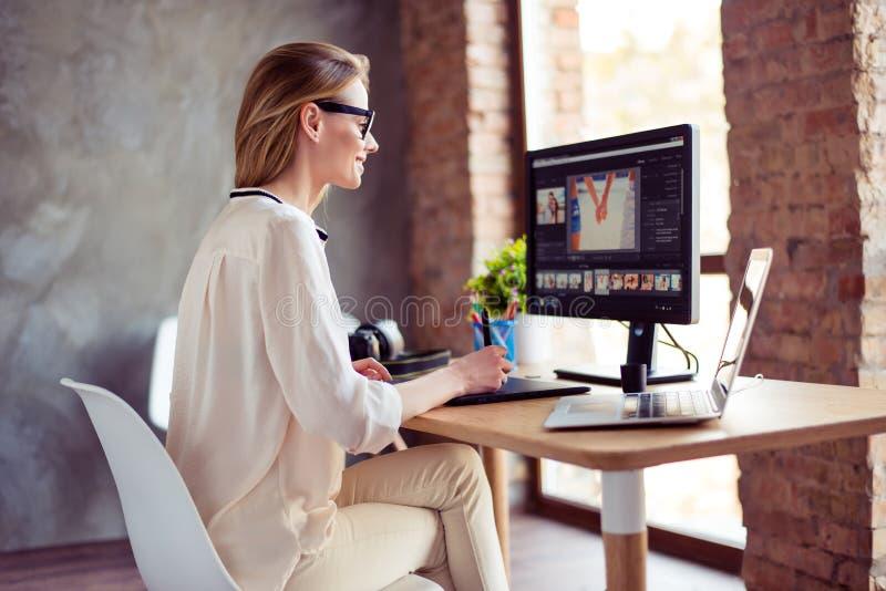 坐在桌a上的年轻满意的微笑的妇女画象  免版税库存照片