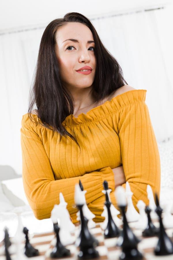 坐在棋-不确定性前面的黄色礼服的妇女 免版税库存照片