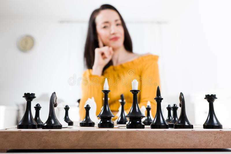 坐在棋-战略前面的黄色礼服的妇女 免版税库存照片