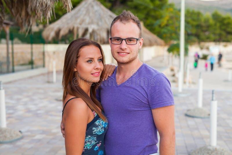 坐在棕榈树附近和花费了不起的时间的夫妇 免版税库存照片