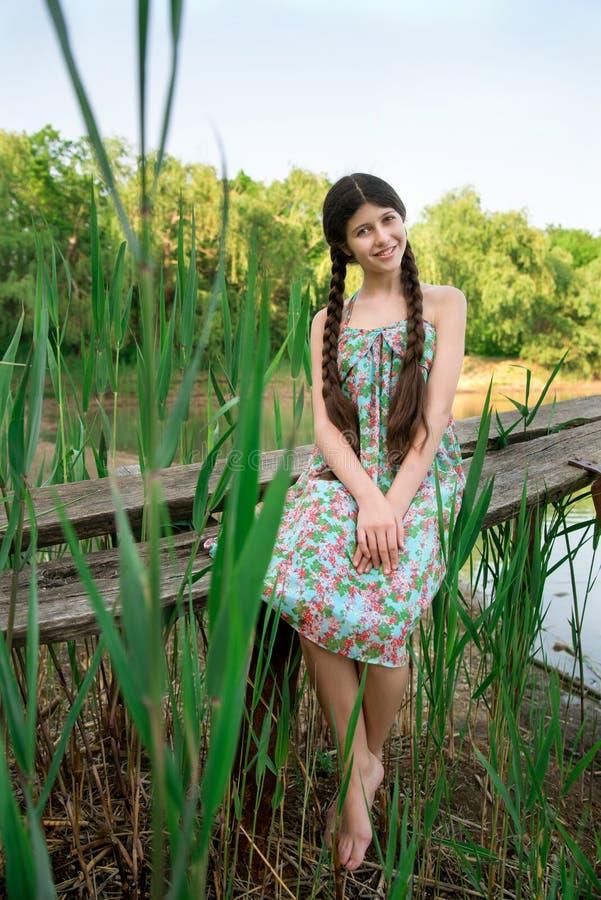 坐在森林前面湖的好女孩 免版税图库摄影