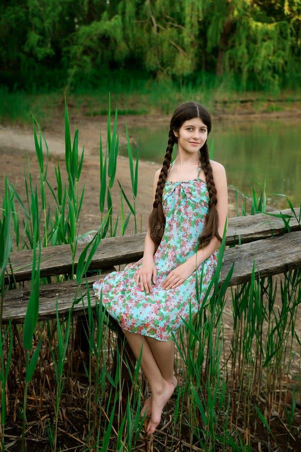 坐在森林前面湖的好女孩 免版税库存照片