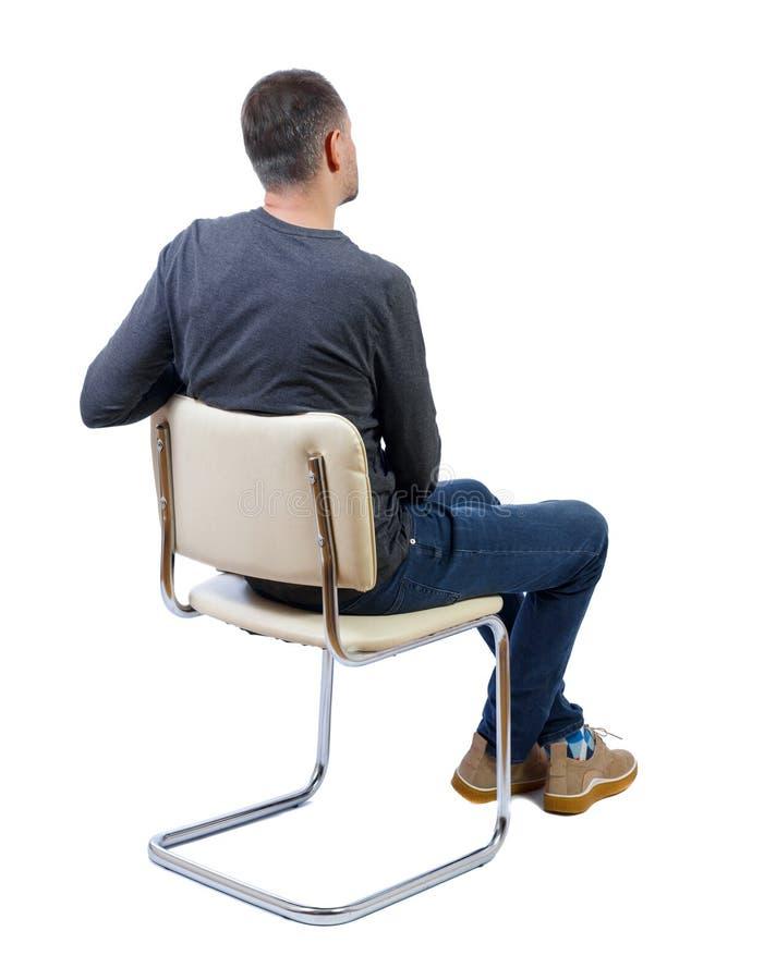 坐在椅子上的男人的侧视图 免版税图库摄影