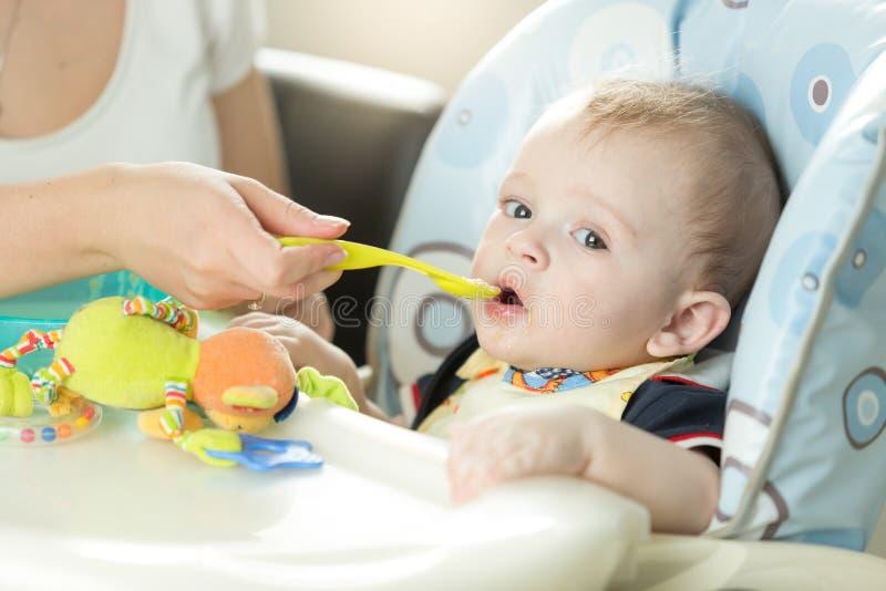 坐在椅子和吃f的逗人喜爱的可爱男婴画象  免版税库存图片