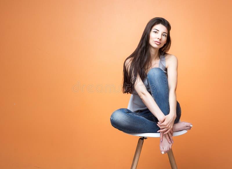 坐在椅子和调查照相机的一个女孩的画象反对橙色背景 生活方式和人概念 免版税库存照片