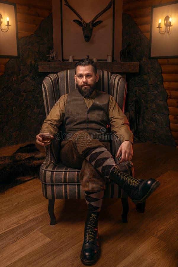坐在椅子和饮料威士忌酒的猎人人 库存图片