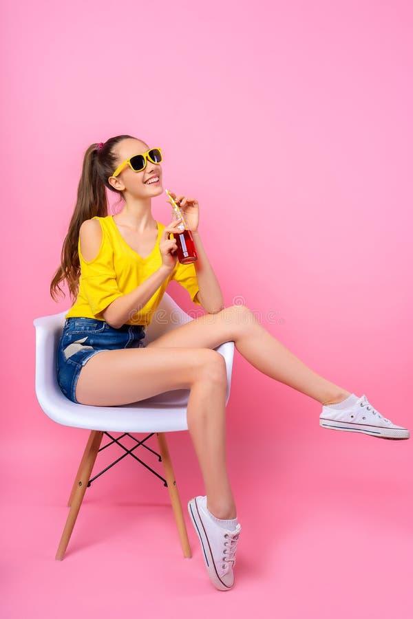坐在椅子和饮用的饮料的十几岁的女孩 免版税库存图片