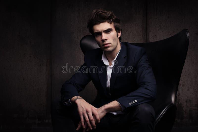 坐在椅子的一个美丽的年轻人的画象 时髦在出现上 免版税库存照片