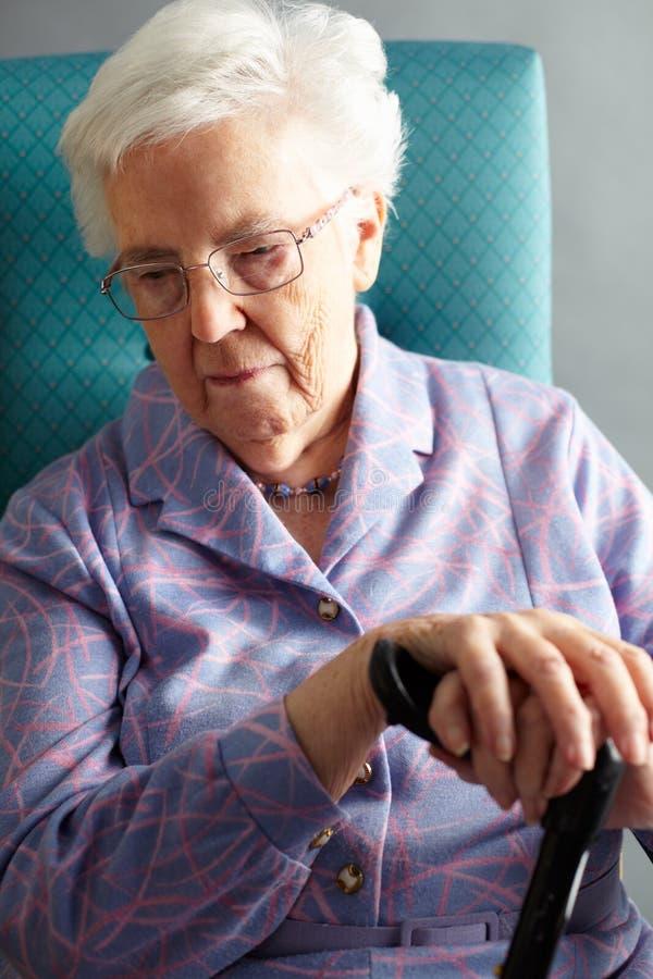 坐在椅子的不快乐的高级妇女 图库摄影