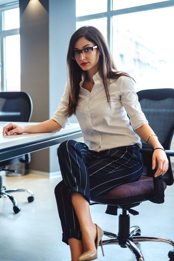 坐在椅子的严肃的女商人在办公室 库存图片
