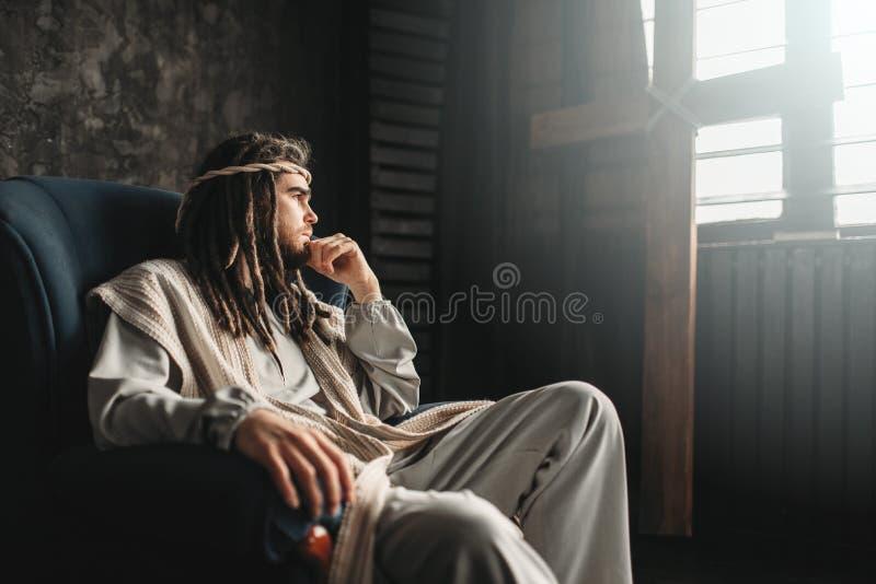 坐在椅子的体贴的耶稣基督 免版税图库摄影
