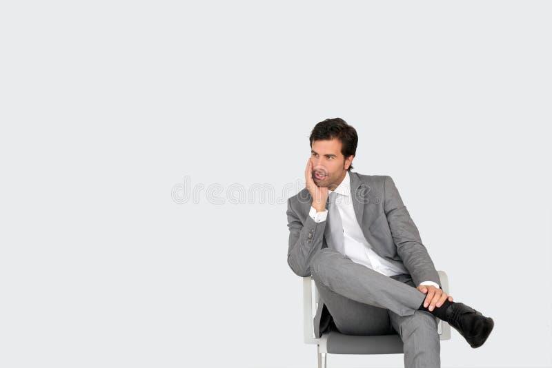 坐在椅子的商人被隔绝 免版税库存照片