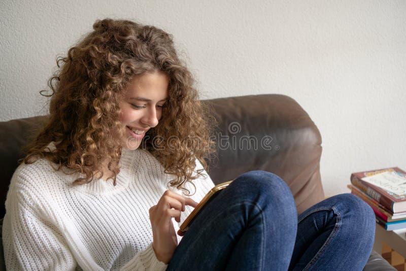 坐在椅子的女性少年是繁忙的与她的数字式p 免版税库存图片