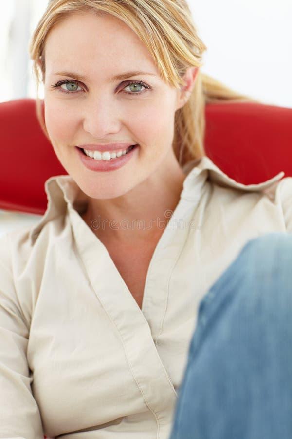 坐在椅子的妇女纵向 库存照片