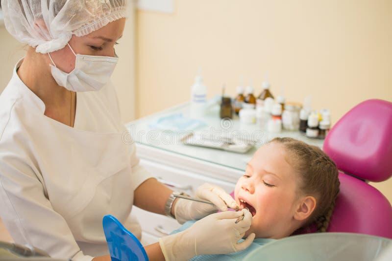 坐在椅子的小逗人喜爱的女孩在牙医诊所在牙齿核对和治疗期间 免版税库存照片