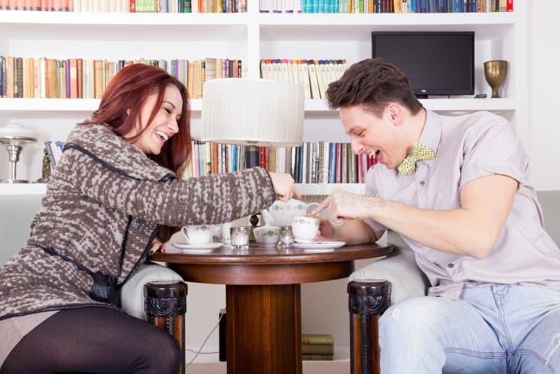 坐在椅子的微笑的夫妇在客厅 图库摄影