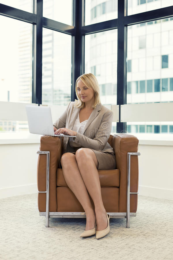 坐在椅子的快乐的女商人 研究膝上型计算机在现代办公室 免版税图库摄影