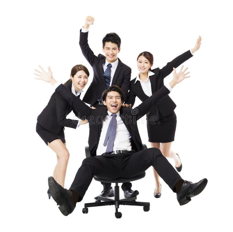 坐在椅子的愉快的集团推挤同事 免版税库存照片