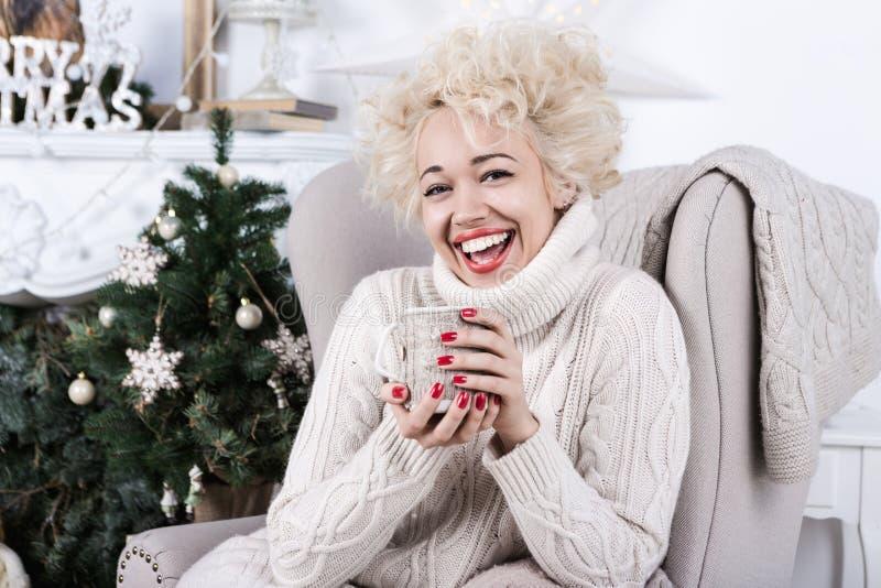 坐在椅子的笑的女孩 球圣诞节查出的心情三白色 库存照片