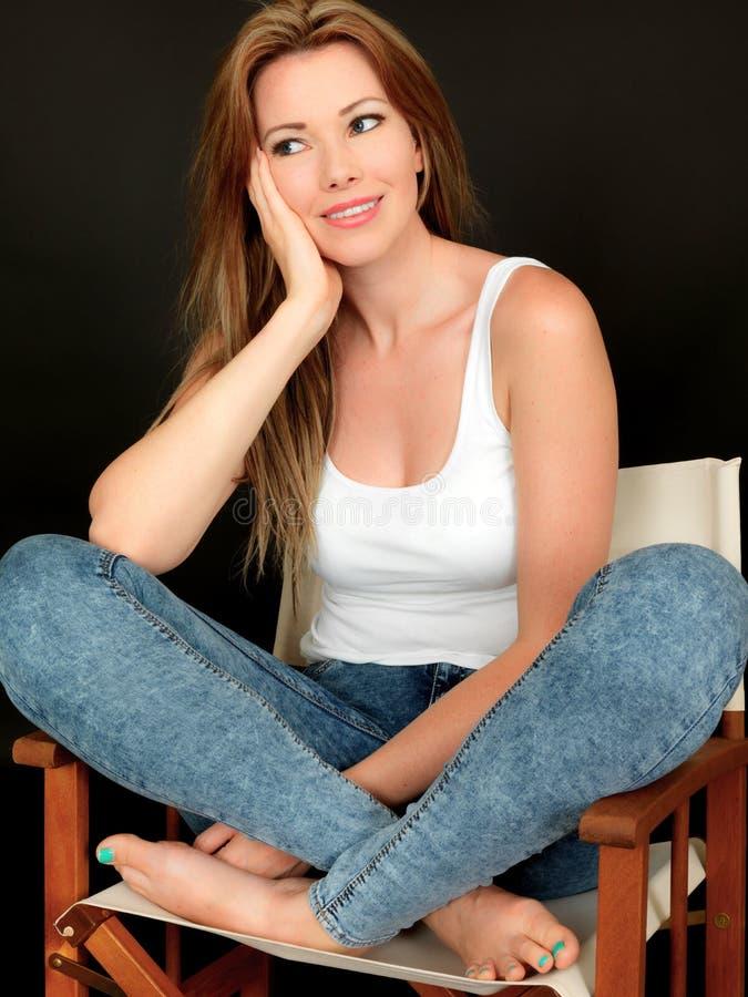 坐在椅子的美丽的愉快的轻松的少妇 图库摄影
