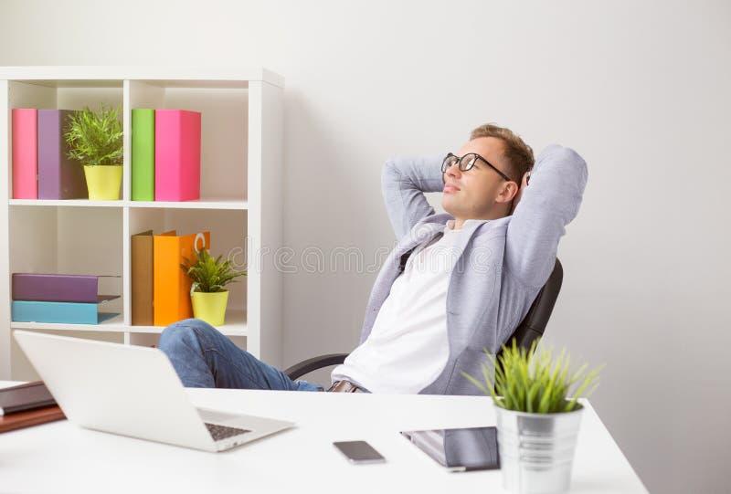 坐在椅子的轻松的商人用在头后的手 免版税库存照片