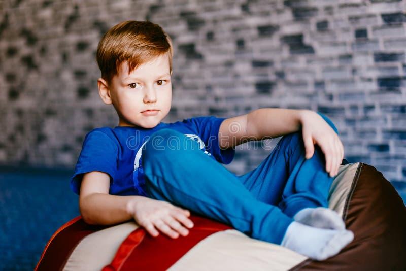 坐在椅子袋子的严肃的男孩 免版税库存照片