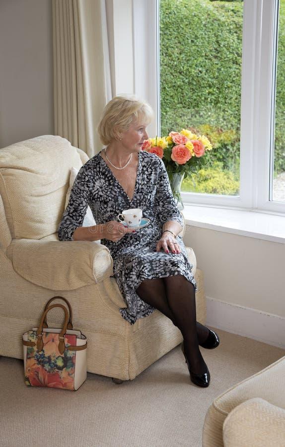 坐在椅子饮用的茶的年长夫人 库存照片