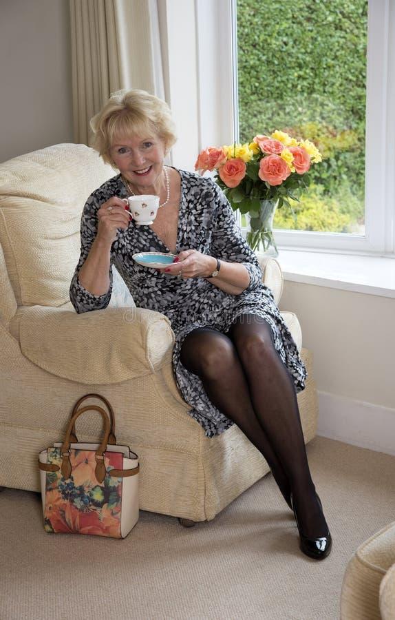 坐在椅子饮用的茶的年长夫人 免版税库存图片
