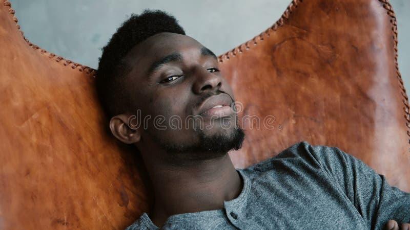 坐在椅子,微笑和看直接照相机的非洲人画象 男性看起来梦想,周道和镇静 库存图片