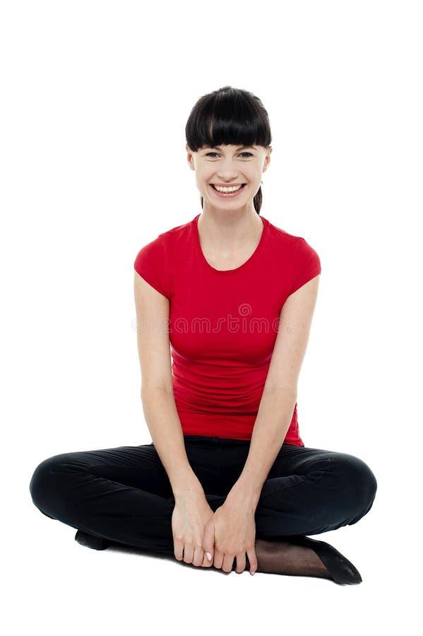 坐在楼层的轻松的微笑的时髦妇女 免版税库存图片