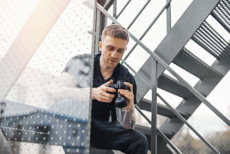 坐在楼梯和检查照片秘密审议的可爱的人 免版税库存图片