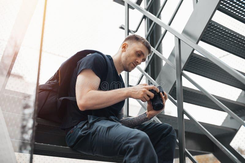坐在楼梯和检查照片秘密审议的可爱的人 库存照片