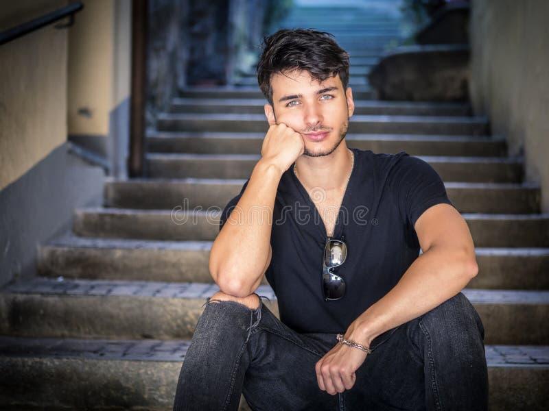 坐在欧洲城市胡同的英俊的年轻人 库存图片
