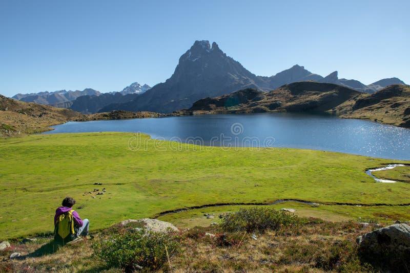 坐在比利牛斯山的妇女徒步旅行者在Pic du密地d Ossau附近 库存图片