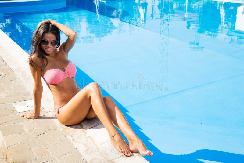 坐在比基尼泳装近的游泳水池的迷人的妇女 免版税库存照片